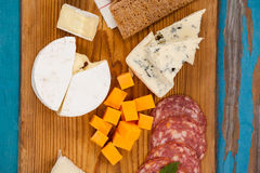 Cheese with ham and crispy biscuits on chopping board Royalty Free Stock Images
