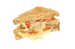 Cheese ham and tomato sandwich. Toasted cheese, ham and tomato sandwich with stringy cheese isolated against white Royalty Free Stock Photo