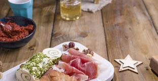 Cheese and ham on the wooden table. Christmas snacks and free space for the text stock photos