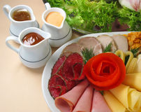 Cheese and hams. Cheese and different hams on the white plate Royalty Free Stock Photography