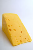 Cheese hard sector. Sector of hard cheese on a light background close-up Stock Images