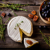 Cheese, herbs, nuts and grape on dark wooden table. Royalty Free Stock Photography