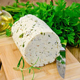 Cheese homemade with herbs and knife on board. Homemade cheese with herbs and spices, knife, parsley, rosemary, vegetable oil in a bottle on a wooden board stock photography