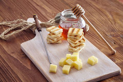 Cheese and honey appetizer. On a chopping board Royalty Free Stock Images