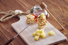 Cheese and honey appetizer. On a chopping board Royalty Free Stock Image