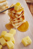 Cheese and honey appetizer. On a chopping board Royalty Free Stock Photos