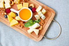 Cheese, honey, berries and nuts. On wodden board Stock Images