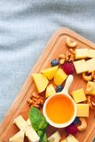 Cheese, honey, berries and nuts on wodden board Stock Photo