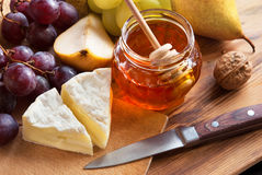 Cheese with Honey. Cheese Camembert with honey, pear, walnut and grapes Royalty Free Stock Images