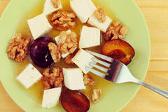 Cheese with honey, plum and walnut, toned effect Royalty Free Stock Images