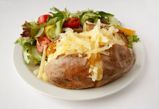 Cheese Jacket Potato with side salad. A Cheddar cheese baked potato on a plate with side salad Royalty Free Stock Photography