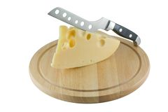 Cheese on the kitchen board and knife for cheese Royalty Free Stock Photos