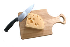 Cheese and knife on bread board Royalty Free Stock Photos
