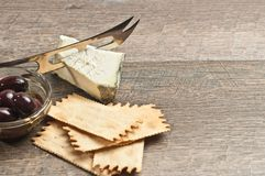 Cheese knife cutting into wedge of cheese with negative space-right Royalty Free Stock Photos