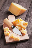 Cheese knife and fork. Hard, ripened parmesan or grana padano cheese on wooden board Royalty Free Stock Images