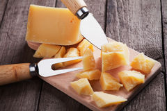 Cheese knife and fork. Hard, ripened parmesan or grana padano cheese on wooden board Royalty Free Stock Image