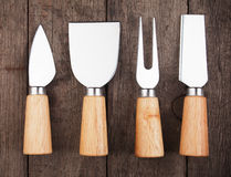 Cheese knives and fork. Set of cheese knives and fork on wooden table Stock Image