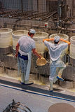 Cheese makers at work during the processing of Gruyere cheese Stock Image