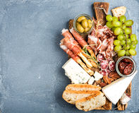 Cheese and meat appetizer selection. Prosciutto di Parma, salami, bread sticks, baguette slices, olives, sun-dried Royalty Free Stock Photo