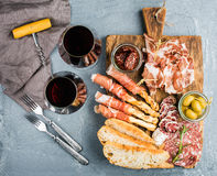 Cheese and meat appetizer selection or wine snack set. Variety of  cheese, salami, prosciutto, bread sticks, baguette Stock Image