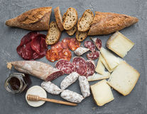 Cheese and meat appetizer selection or wine snack set. Variety of italian cheese, salami, bresaola, baguette, honey on Stock Images