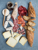 Cheese and meat appetizer selection or wine snack set. Variety of italian cheese, salami, bresaola, baguette, honey on Stock Photos