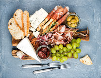Cheese and meat appetizer selection or wine snack set. Variety of  , salami, prosciutto, bread sticks, baguette, honey Royalty Free Stock Photography