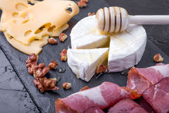 Cheese and meat plate with walnuts on black slate plate background. Camembert with honey Stock Photo