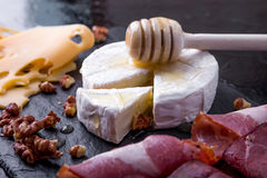 Cheese and meat plate with walnuts on black slate plate background. Camembert with honey Royalty Free Stock Photography
