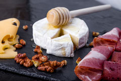 Cheese and meat plate with walnuts on black slate plate background. Camembert with honey Stock Photos