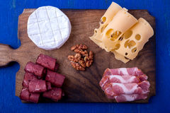 Cheese and meat plate with walnuts on blue wooden background. Top view. Stock Photography