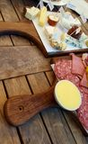 A cheese and meat platter. A cheese and meat platter served on wooden boards Stock Photography