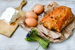 Cheese, milk, bread and eggs. Breakfast of  organic  bio cheese, milk, home made vetable  bread and eggs on a  white wooden background Stock Image