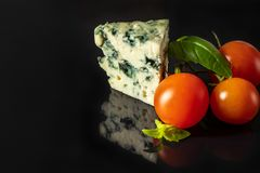 Cheese with mold with red cherry tomatoes and Basil royalty free stock photography