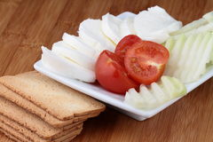 Cheese mozzarella. And tomato on white plate with crackers Stock Image