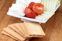 Cheese mozzarella. And tomato on white plate with crackers Royalty Free Stock Photos