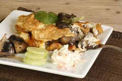 Cheese and mushroom omelette. With coleslaw mushrooms and cucumber on a wooden table Royalty Free Stock Photography