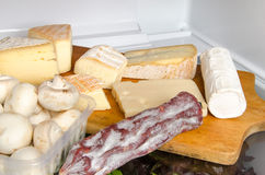 Cheese, mushrooms and a sausage inside a refrigerator Royalty Free Stock Photo
