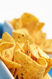 Cheese Nacho Chips. Some cheese flavored tortilla/Nacho chips on snack bowls on white background. Shallow DOF, focus on the close end Royalty Free Stock Photography