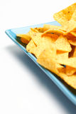 Cheese Nachos. Some cheese flavored tortilla/Nacho chips on a large snack plate on white background. Shallow DOF, focus on the far end Stock Photography
