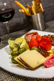 Cheese, nut and meat plate with bread sticks and red wine Stock Images