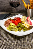 Cheese, nut and meat plate with bread sticks and red wine Royalty Free Stock Images
