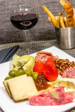 Cheese, nut and meat plate with bread sticks and red wine Royalty Free Stock Photos