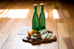 Cheese, nuts, dried apricots, mandarins, and two bottles of water on the wooden floor Stock Image