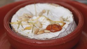 Cheese with nuts and honey on ceramic dish stock video footage