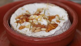 Cheese with nuts and honey on ceramic dish stock footage