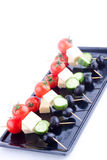 Cheese and olive canapes with tomato and cucumber Stock Image