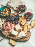 Cheese, olives, prosciutto, baguette slices, grapes and red wine Royalty Free Stock Photography