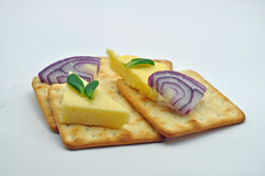 Cheese onion and crackers. Cheese onion on crackers with herb garnish, against a light blue black ground Royalty Free Stock Photo