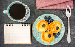 Cheese pancake with blueberries, coffee and notebook top view Stock Photo
